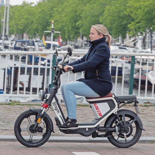 Vrouw op op AGM rijdende scooter op een brug