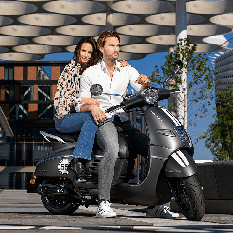 Man en vrouw zittend op een Peugeot scooter