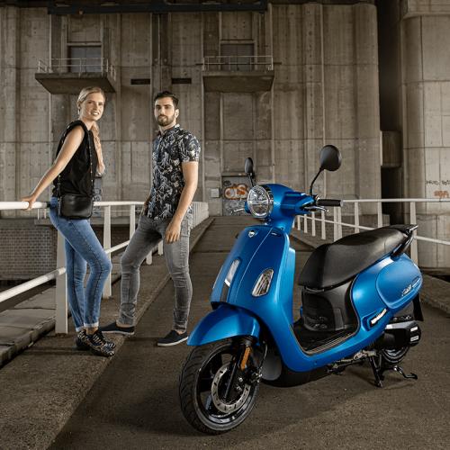 Vrouw en man aan het poseren achter een blauwe scooter
