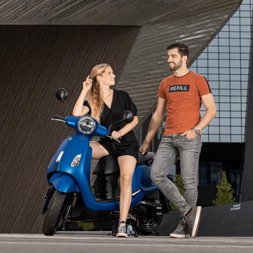 Man lachend naar een poserende vrouw op blauwe scooter voor Rotterdam Centraal