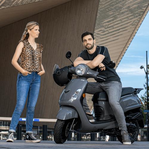Vrouw staand naast poserende man op scooter voor Rotterdam Centraal